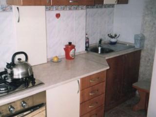 Белый шкафчик на стене закрывает газовую трубу с краном и позволяет повесить в него прихватки.